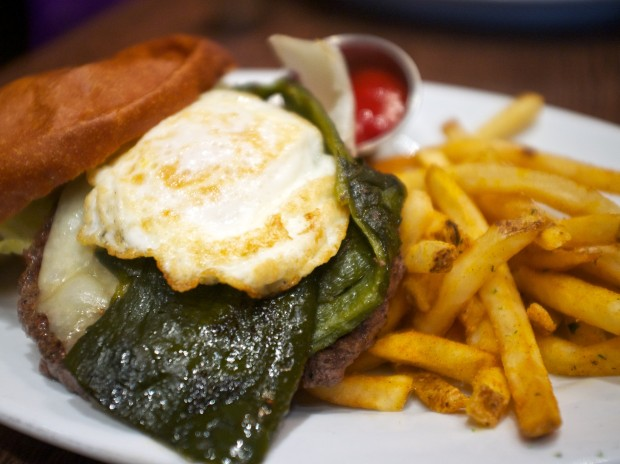 An angus chuck patty, manchego cheese, roasted poblano chile, tomato, lettuce, fried egg, and house sauce on a toasted brioche. $14.99