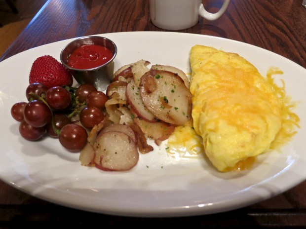 A Ham and cheese omelet served with cafe breakfast potatoes and fruit. $9.99