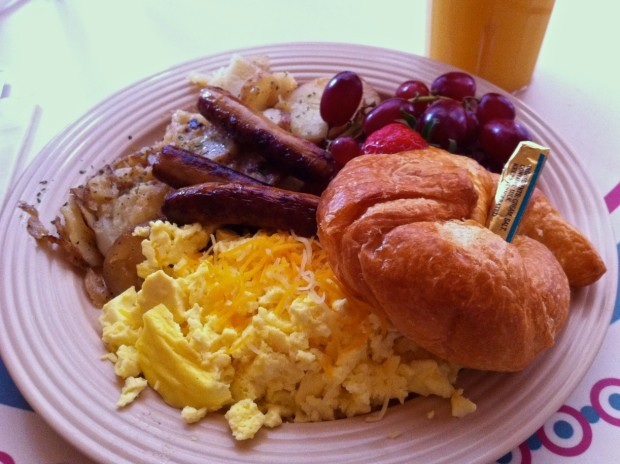Carnation Café Review Scrambled eggs with cheddar cheese, Oscar's potatoes, a croissant and your choice of bacon or sausage with fresh fruit in 2012. $9.99