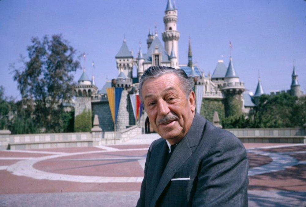 Walt Disney posing in front of Sleeping Beauty's castle