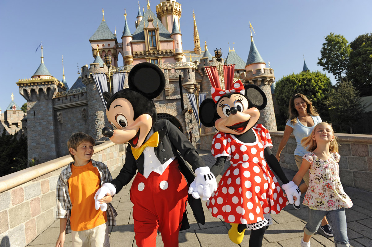 Mickey and Minnie Mouse holding hands with a family
