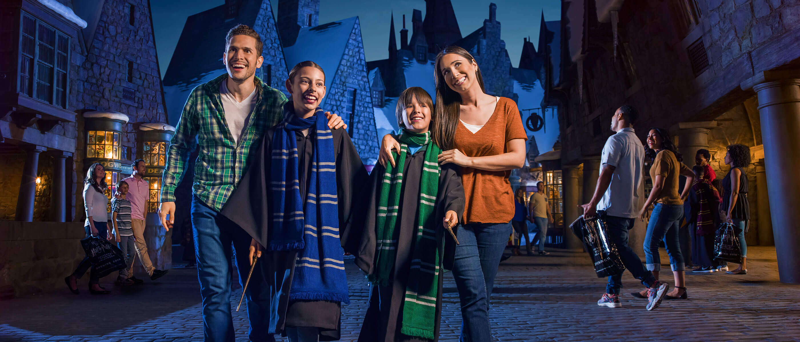 Family of four in Harry Potter house robes walking in Universal Studios