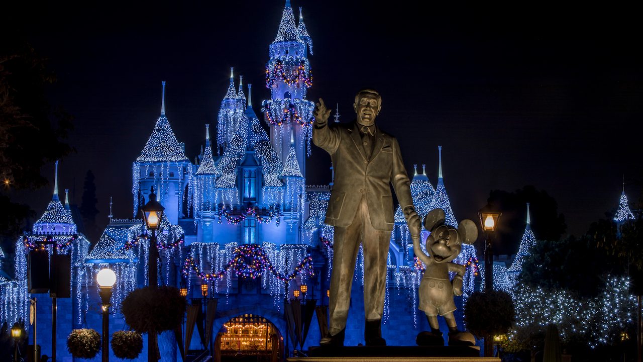 Disneyland at Christmas with the castle light up in front of the partners statue