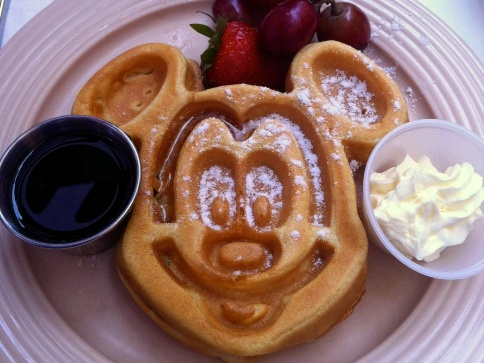 A Mickey-Shaped waffle served with hickory-smoked bacon or chicken-apple sausage links. $10.49 You can add apple or strawberry topping for 0.99. In 2012 you use to get one large Mickey-Shaped Waffle