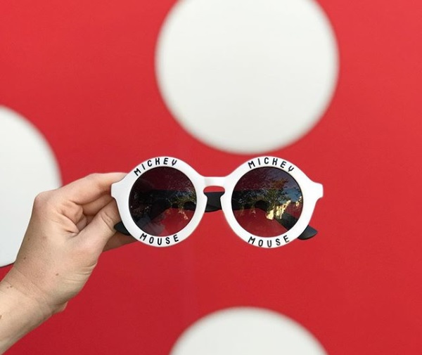 red and white polka dot wall with someone holding sunglasses in front of it