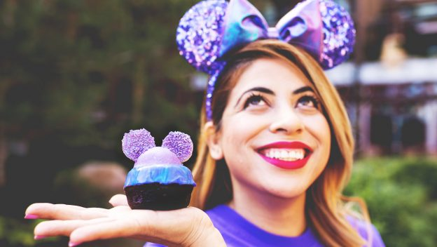 Girl holding Purple cupcake while wearing purple minnie ears