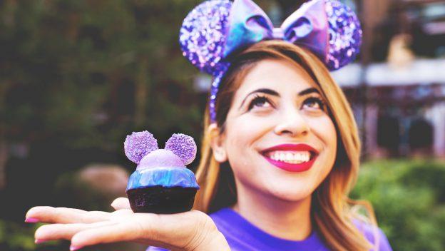 Girl holding Purple cupcake while wearing purple minnie ears
